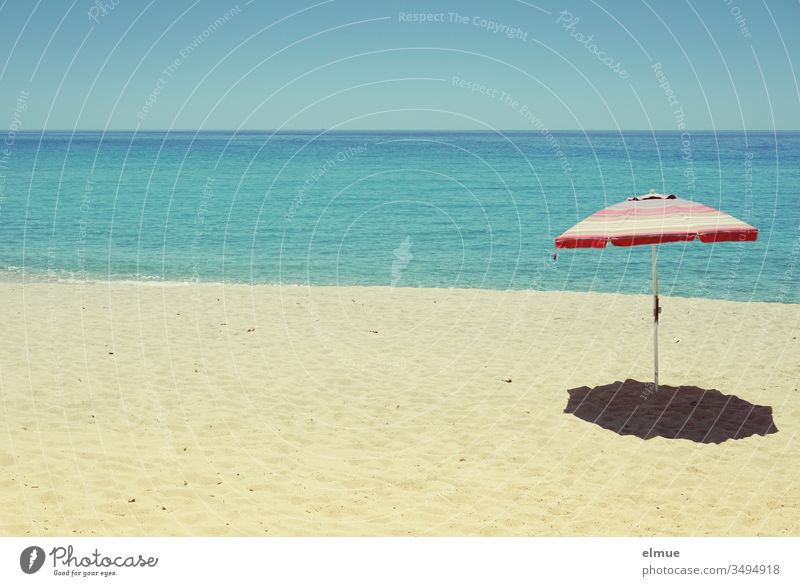 empty sandy beach with a parasol in front of blue sea in sunshine Sandy beach Beach Wanderlust Ocean Sunshade Deserted Water Empty orphan Summer