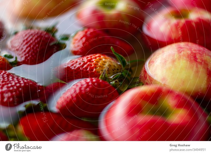 Close-Up of Fresh Organic Strawberries and Apples Floating in Water Strawberry organic fruit Organic produce Colour photo Vegetable healthy vegan