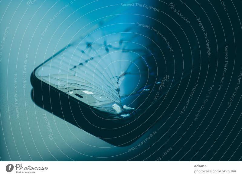 Smartphone with broken screen on black desktop Screen smartphone Mobile Telephone Glass cell Broken Technology Equipment Cellphone Gadget Display Communication