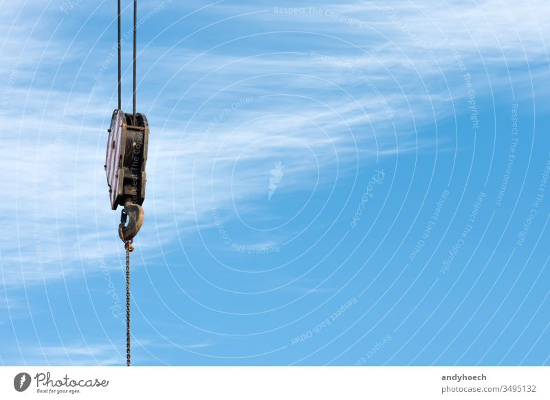 A hook of a crane with blue sky as a background at work Background building industry built structure cable cloud clouds cloudy connecting construction