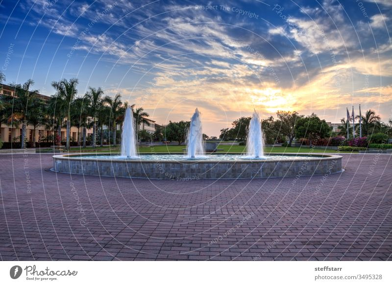 Sunset over a fountain with three sprays in a reflective pool landscape sky clouds Water fountain reflective pond water beauty relaxing tranquil green grass