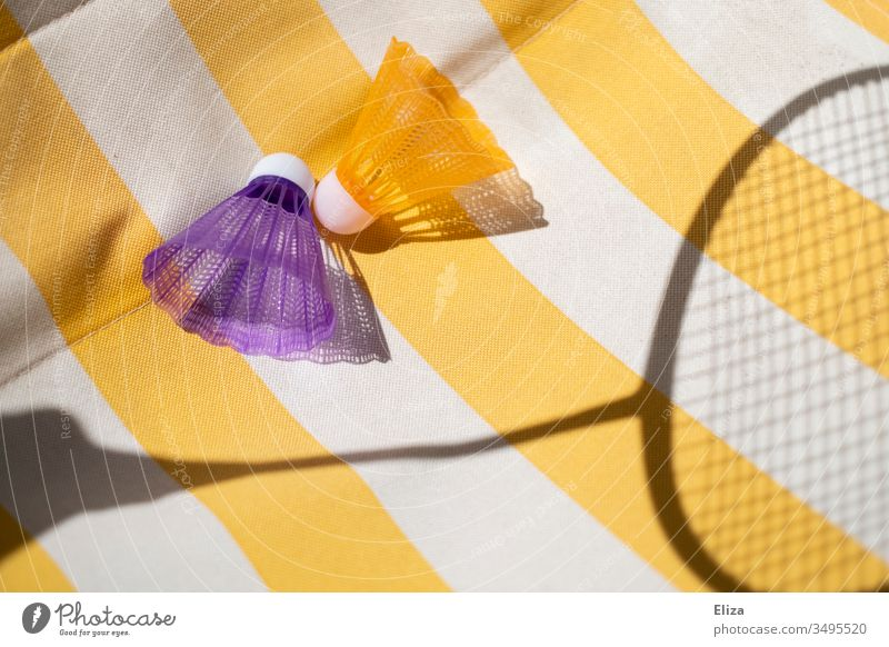 Two colourful shuttlecocks with the shadow of a badminton racket on a yellow and white striped background Shuttlecock badminton rackets Yellow White Shadow