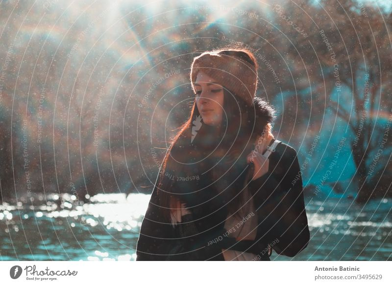 Attractive brunette in winter clothing and an orange head scarf posing on a cold winter day with eyes closed. Water droplets flying everywhere creating a mist,fog and mini rainbows