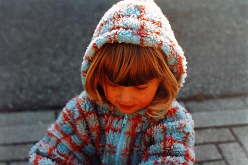 Girl in a checked fleece cuddly jacket, playing, happy, carefree and cheerful, with hood on her head, as weather protection, out on the street in autumn.