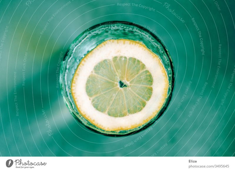 A glass of sparkling water with a slice of lemon from above on a turquoise green background Water Tumbler Slice of lemon Glass fizz fizzy Blur Round