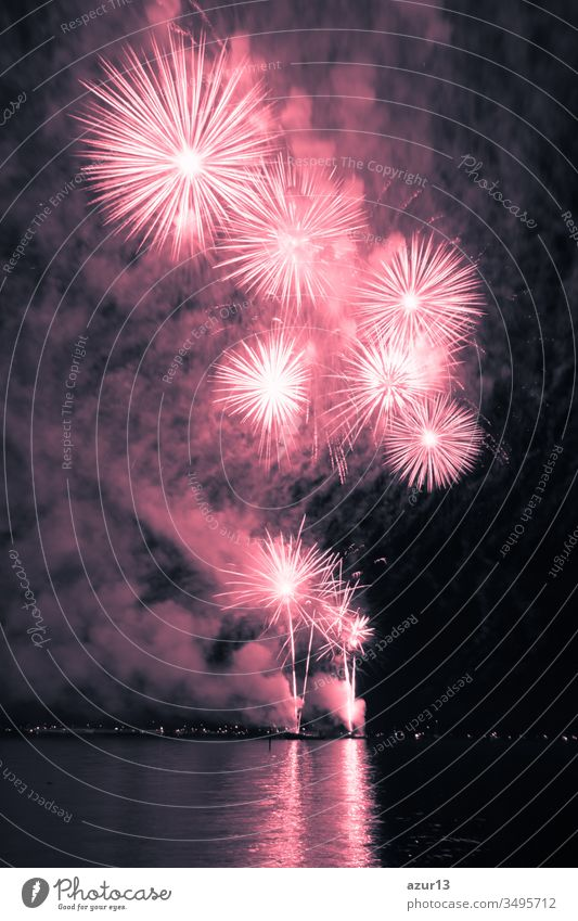 Luxury fireworks event sky water sea show with red stars. Premium entertainment magic star firework at e.g. New Years Eve or Independence Day party celebration. Nice lake surface reflections