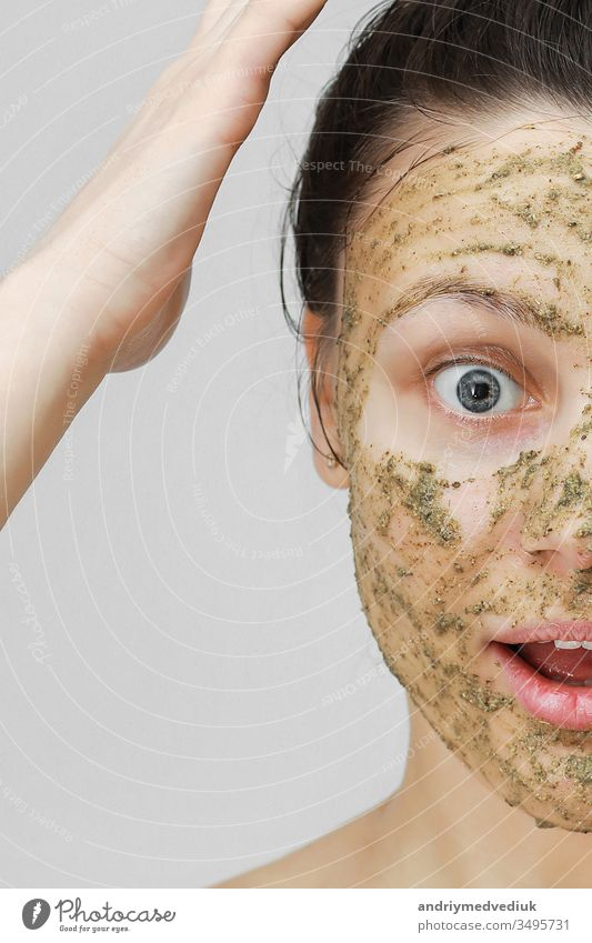 Skin Care. Cosmetic Day. young girl in home style, her hair gathered with her hands at the top. With eco, herbal, natural mask, green on the face. Front view.
