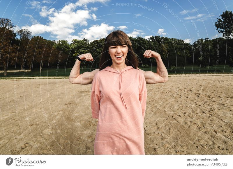 Sporty energetic athletic woman wears pink sports top smiles as shows her biceps, likes sport and active lifestyle. athlete muscle fitness adult background