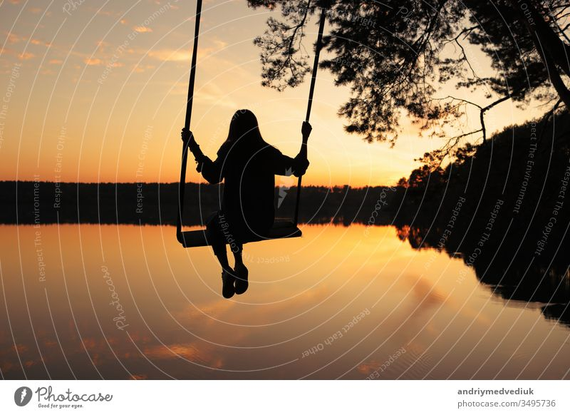 romantic young woman on a swing over lake at sunset. Young girl traveler sitting on the swing in beautiful nature, view on the lake swinging summer boy