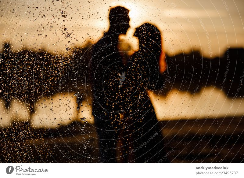 silhouette of loving couple hugging on the lake at sunset. Beautiful young couple in love walking on the shore of the lake at sunset in the rays of bright light. copy space. selective focus