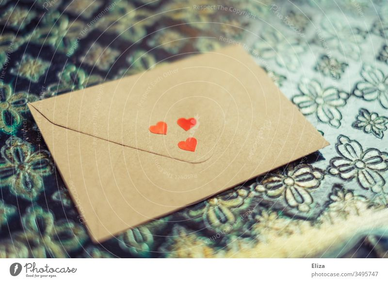 An envelope decorated with three red hearts, which lies on an ornamental background; love letter Envelope (Mail) Mother's Day cuddle Love Letter (Mail) Gift