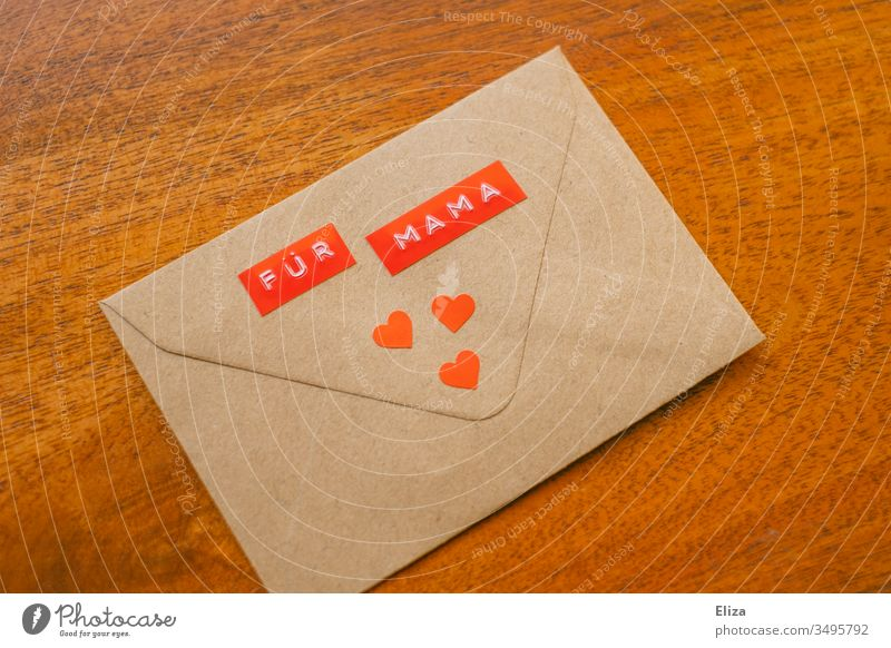 An envelope on the For Mama stands decorated with three red hearts on a wooden background; message gift to the mother on Mother's Day mama Envelope (Mail)
