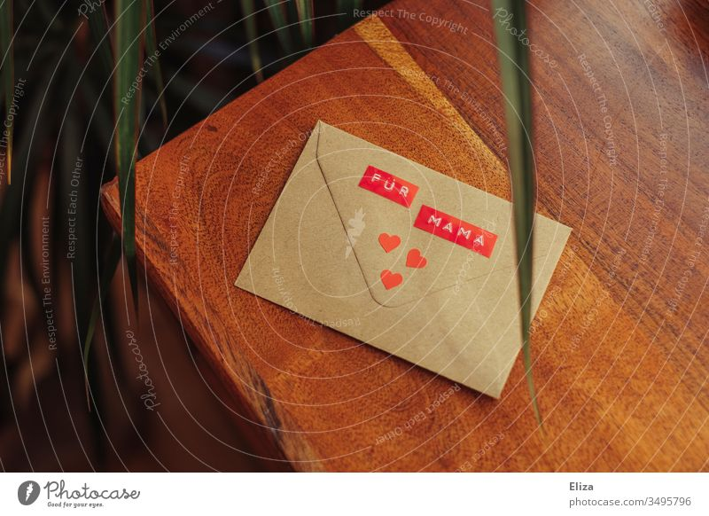 An envelope on the For Mama stands decorated with three red hearts on a wooden background; letter gift to the mother on Mother's Day mama Envelope (Mail) cuddle