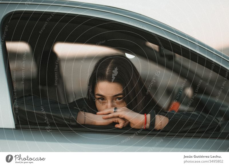 young girl leaning against the window of a gray car Human being Driver Travel photography Portrait photograph Vintage girls Life coche Beautiful Cute Model