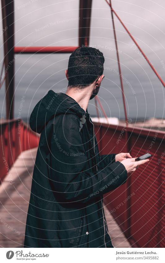 man in a black coat holding a mobile phone on a red bridge Day Town Bridge building Vacation & Travel Architecture Bridge pier Sky City trip Colour photo