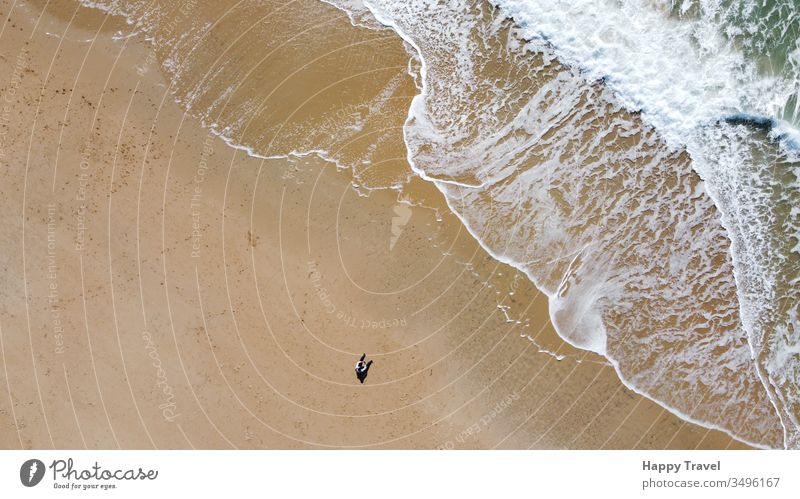 Aerial view of a sand beach. A man is sat on the sandy looking at the wave breaking close to him. Sunny day sunny day waves sea ocean orange loneliness