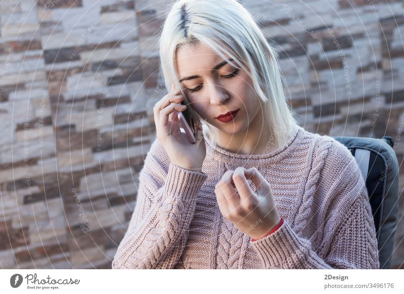 Young, pretty woman talking on cellphone while sitting on sofa on terrace 1 female mobile mobile phone home outdoors casual attire adult caucasian holding young