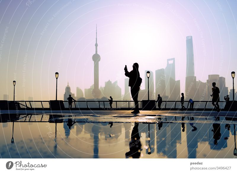 traveler take a photo of morning activity at the bund, huangpu riverside,  shanghai city view background ancient architecture beautiful building business china