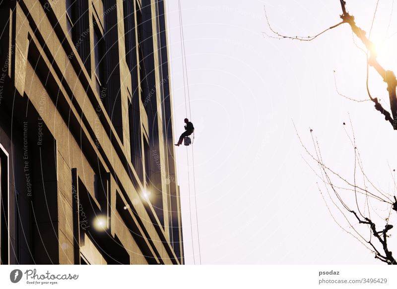 worker cleaning outdoor windows service on high rise building blue business city cleaner climb climbing danger dangerous exterior facility glass grid group