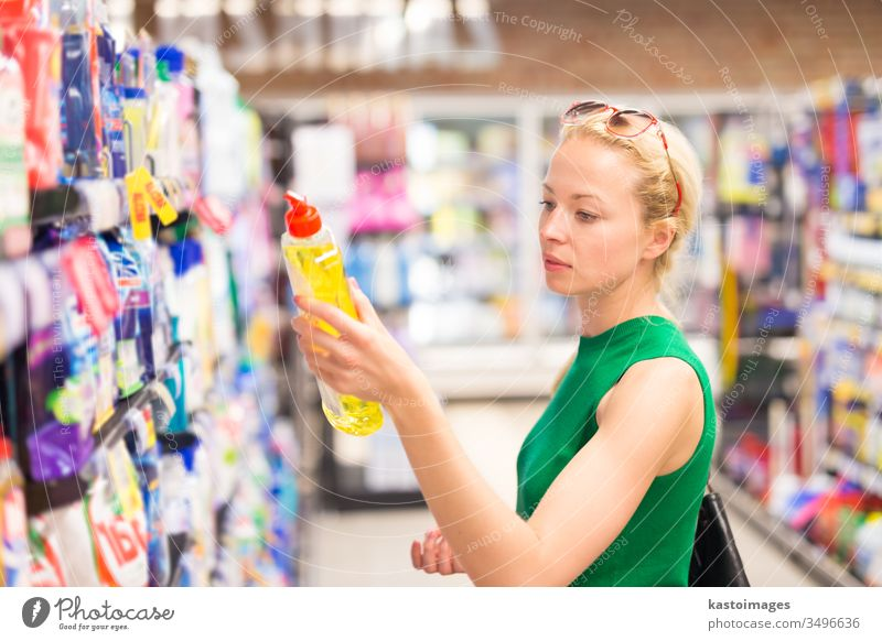 Woman shopping cleaners at supermarket. store customer consumer basket people young detergent soap washing powder person buy woman commerce adult lifestyle