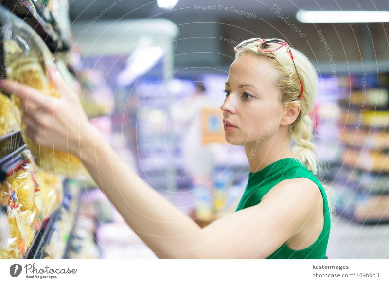 Woman shopping groceries at supermarket. grocery store customer gnocchi consumer woman basket food people young person buy commerce adult lifestyle aisle girl