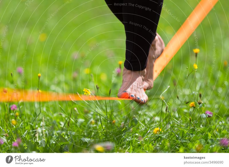 Slack line in the city park. slack line slackline activity sport woman balance tightrope young person fitness back nature concentration walking outdoors skill