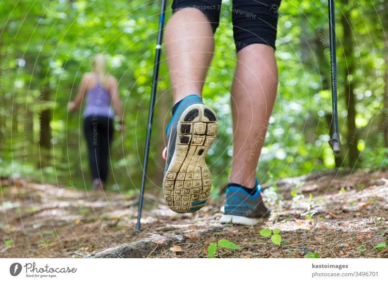 Young couple hiking in nature. Sport and exercise. nordic walking sport trek park people step training jogging adventure woods forest workout leisure female