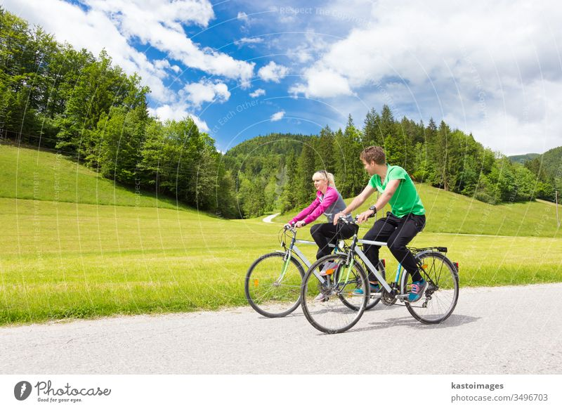 Young spoty active cople biking in nature. Active lifestyle. Activities and recreation outdoors. couple biker cycling cyclist people cycle summer track healthy