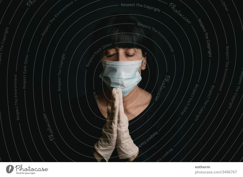 young woman wearing medical mask for coronavirus with hands clasped together praying covid-19 2019-ncov epidemic pandemic quarantine stay home playing prayer
