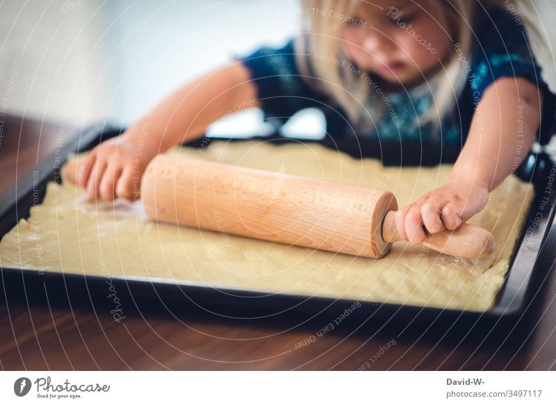 small pizza baker - girl rolls out dough with rolling pin Rolling pin Child Cute concentrated cake Baking Study Roll out Pizza pizza dough