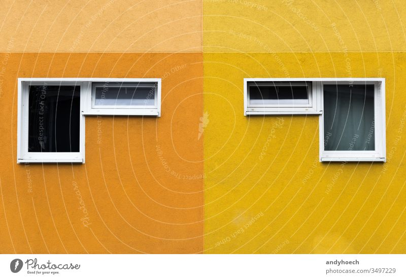 A pair of two windows on a yellow and orange facade abstract apartment architecture Background Berlin building building exterior built structure checkerboard