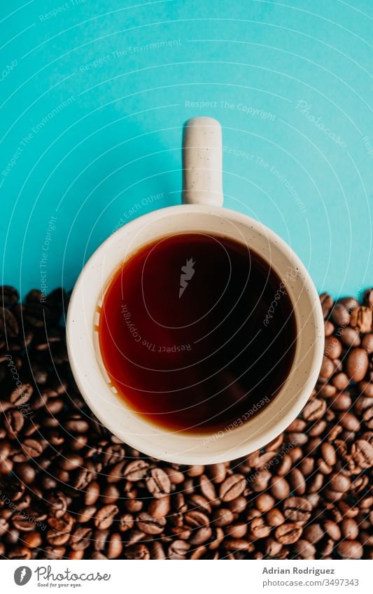 Closeup overhead shot of a cup of coffee with coffee beans on a blue background drink cafe young lifestyle beverage table aroma warm casual mug indoors break