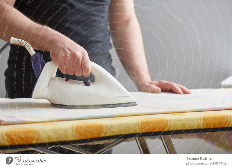 Men's hands hold a white iron and iron on the ironing board. Close-up. Faceless. Copy space. Domestic duties are performed by men. lifestyle housework linen