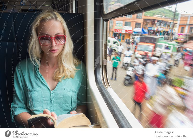 Blonde caucasian woman reading book on train by the window. travel transportation adveture journey indoors relaxing side view vacation on the move sitting