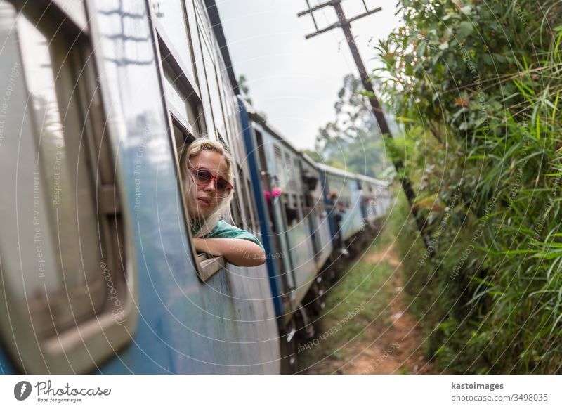 Blonde caucasian woman riding a train, looking trough window. travel transport railway transportation adventure passenger journey indoors relaxing vacation
