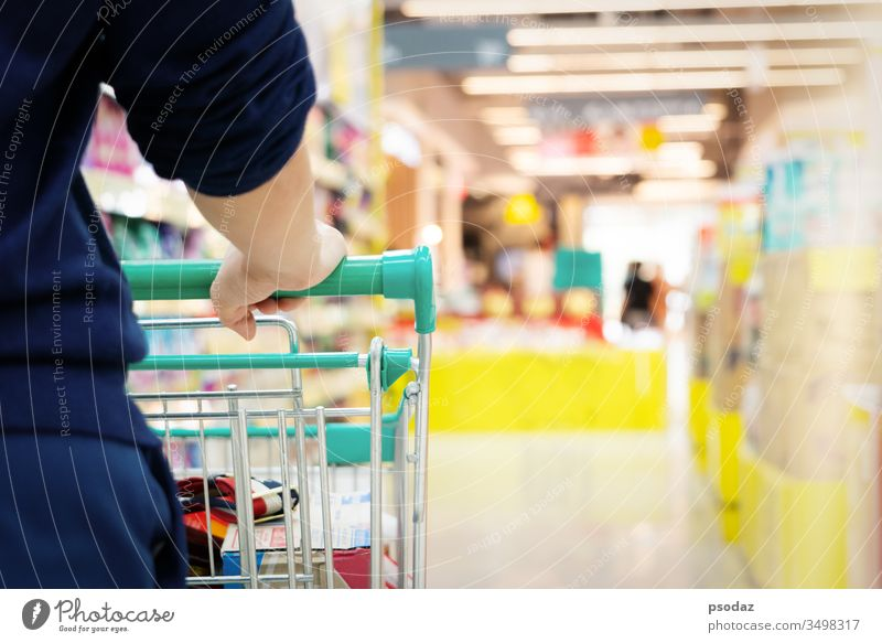 female shopper with trolley with blurred motion of supermarket department store aisle attractive background basket business buy cart city commerce consumer