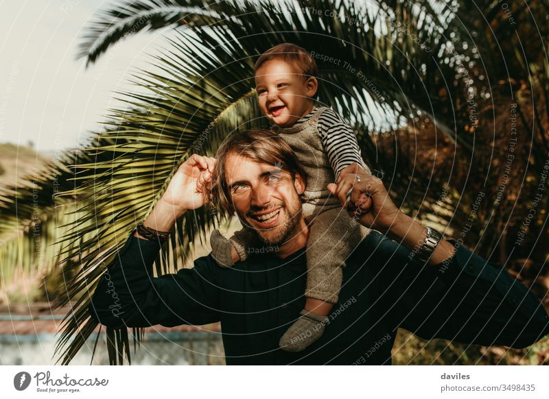 Laughing father giving his son a piggyback ride outdoors with sun light in the face. lovely smile white playing carrying shoulders handsome joyful hipster care