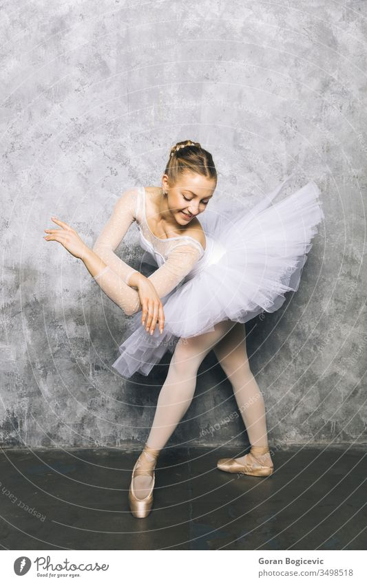 Pretty young ballerina dancer dancing classical ballet against rustic wall woman pose exercise beautiful female shoes dress balance action performer elegance