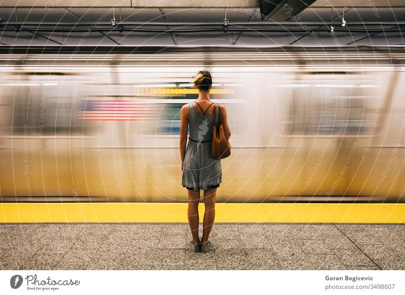 Young woman waiting for subway train in New York City city people metro move transit railroad station underground travel transportation urban girl tunnel motion