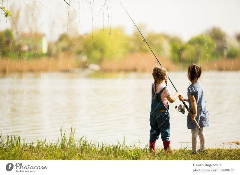 Two little girls fishing activity catch caucasian child childhood cute enjoyment female fisherman fun happiness happy hold kid lake leisure light nature outdoor