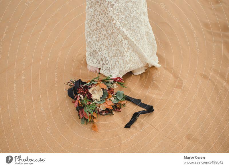 bridal bouquet lying on the sand next to the bride's feet. flower female outside dress outdoors decoration arrangement floral arid climate caucasian romantic