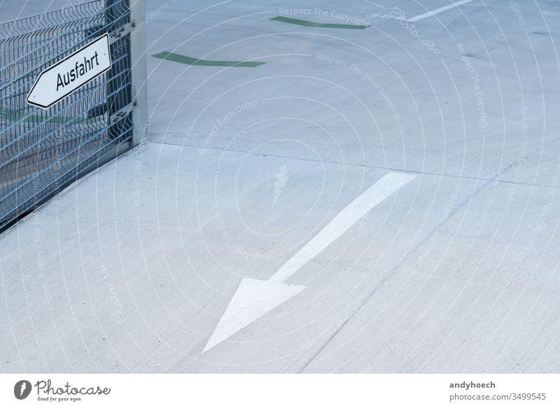 An exit with arrow in a parking garage abstract architecture arrow symbol asphalt Background building cement city communication concept conceptual concrete