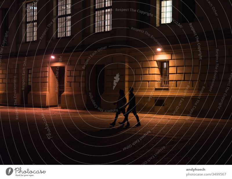 A couple is walking through Berlin at night adult adults architecture building exterior city dark darkness europe friends germany historic history illuminated