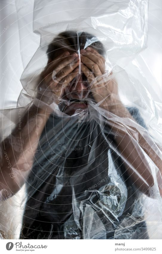 trapped in plastic | a man who is so panicked that he puts his hands in front of his face protective attitude Animosity Frustration Protective mask sb./sth.