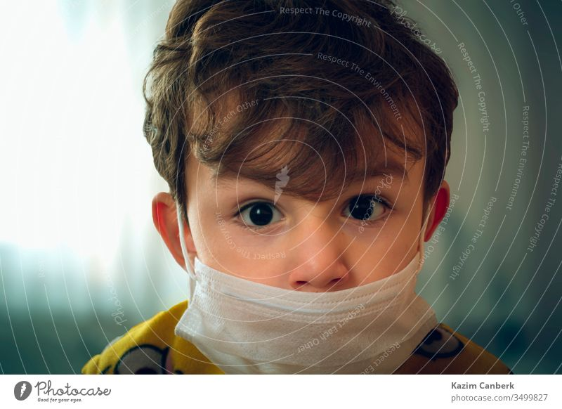 3 years old baby wearing surgical mask peering anxiously at the camera kid corona virus global pandemic epidemic turkey turkish protection curfew prevention