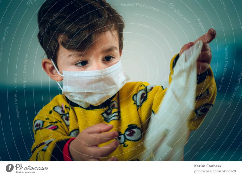 Happy looking 3 years old baby wearing pajamas and mask plays with surgical gloves kid corona virus global pandemic epidemic turkey turkish protection curfew
