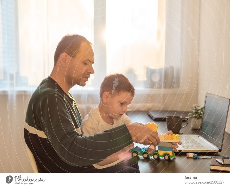 Remote working among children concept working remotely four year old boy play laptop building set dad who works home coronavirus quarantine isolation period