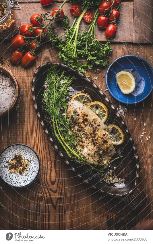 Baked roasted fish fillet in baking form with dill and lemon on wooden background, top view. Home cuisine concept. Seafood, low carb and dieting nutrition baked