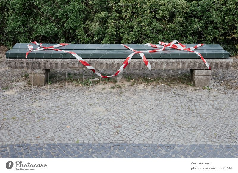 Bank with red and white barrier tape because of Corona Bench cordon Band Red White covid-19 coronavirus pavement Paving stone Wood Green Boxwoods containment