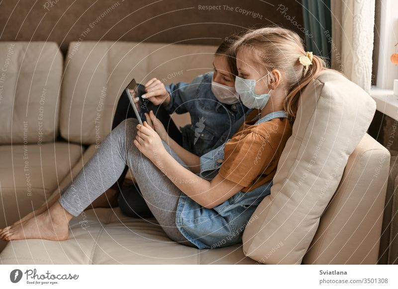 Two cute girls in medical masks are sitting on the sofa with a tablet. Schoolgirls do their homework. Distance learning during the COVID-19 quarantine.